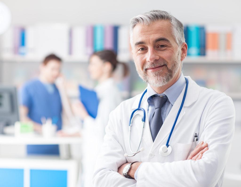Ein Arzt steht in seiner Hausarztpraxis. Dahinter stehen MPAs.